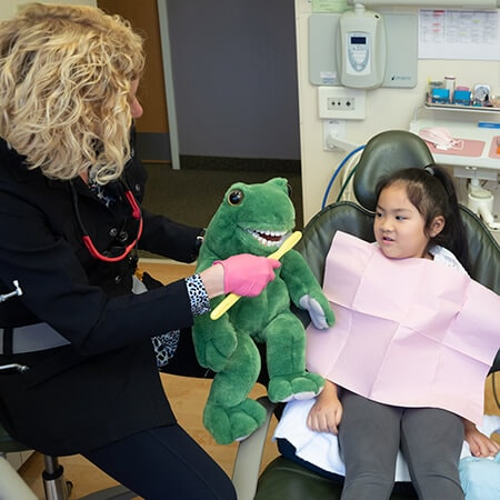 One of our dentists showing a little girl a stuffed frog with a toothbrush