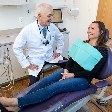 One of our dentists in Reston, VA talking with a female patient who is lying in the dentist's chair