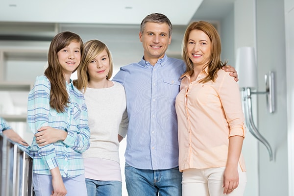 A family of four standing while smiling and hugging after their family dentistry visit