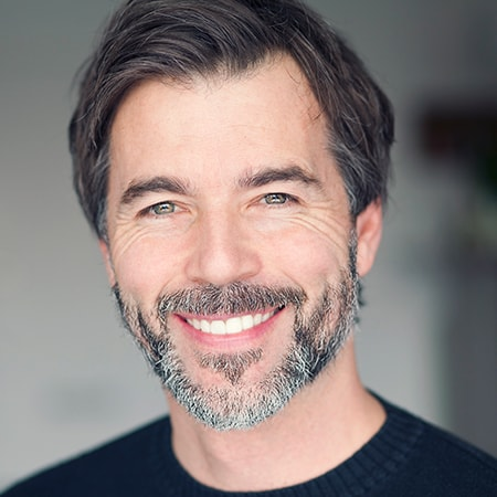 A mature man with a beard wearing a black sweater smiling after his new dentures were fitted