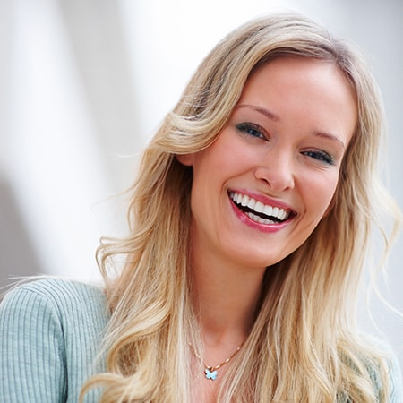 A woman smiling as she shows off her porcelain veneers
