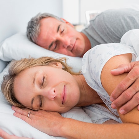 A mature couple sleeping soundly in bed after his snoring treatment