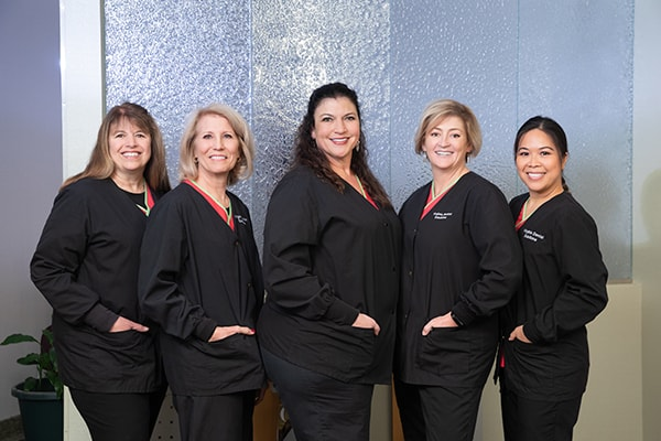 Our Ashburn dentistry team smiling as they wear their black work uniforms