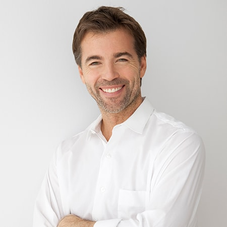 A mature man with brown hair and a beard smiling standing while wearing a white shirt