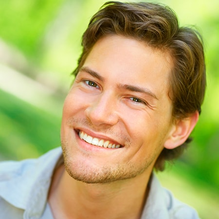 A young man smiling on a bright green background