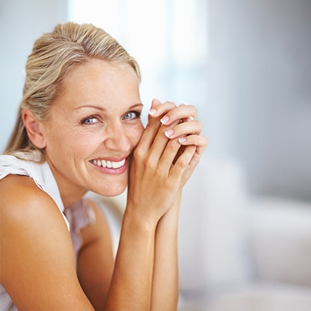 A mature woman smiling as she learns on her hands after her smile design consultation