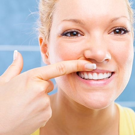 A young blonde woman pulling up her lip to see the work we achieved with laser dentistry