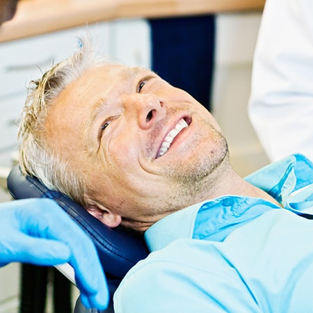 An older man with a beard lying in the dental chair after being fitted for his implant-supported dentures