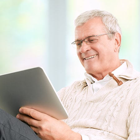 A mature man with glasses looking at his tablet while smiling
