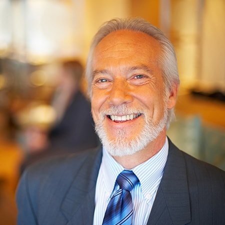 An older business man with a beard wearing a black suit showing off his new dentures
