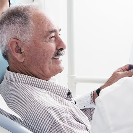 A mature man with a mustache smiling while at his prosthodontics appointment