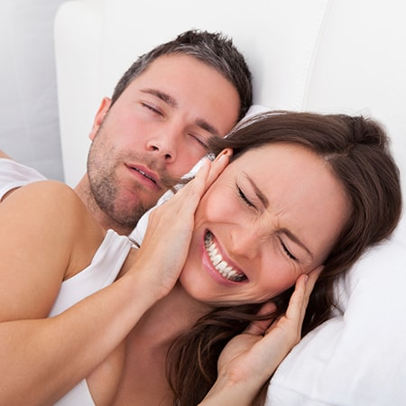 A young man snoring in bed while his partner covers her ears and grimaces