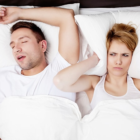 A man is snoring while a woman covers her ears with a pillow