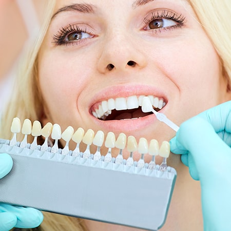 A dentist checking the level of teeth whitening that would best suit a female patient
