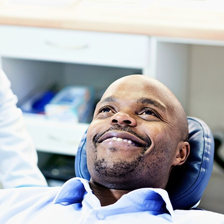 A man lying on the dentist's chair and smiling